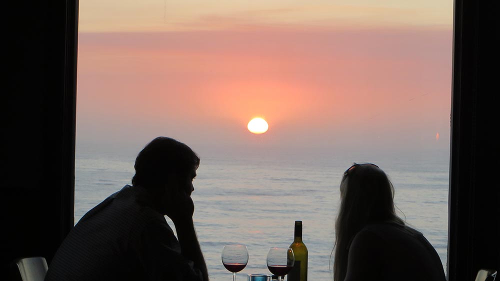Diners Watching Sunset Over Ocean