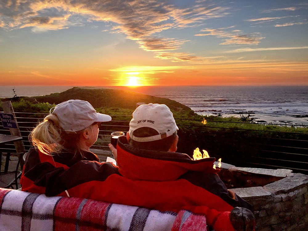 Couple Sitting By Patio Firepit Watching Sunset